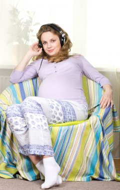 Beautiful pregnant blonde listens to classical music on headphones. Portrait of pregnant woman. The development of the child in the womb