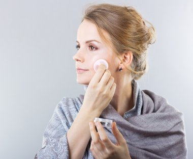 Beautiful blonde caring for her face.Portrait of a beautiful girl. Facials. Pampering. Hair Care