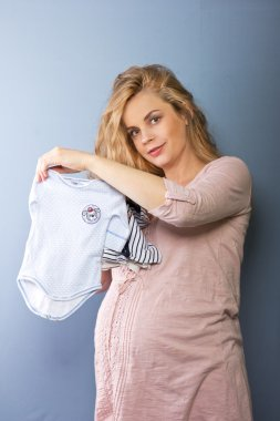 Beautiful pregnant blonde woman with baby clothes. Children's clothes. Pregnant blonde. Portrait of pregnant woman
