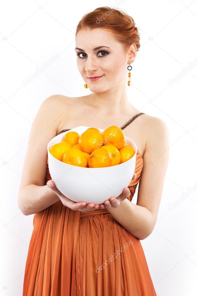8f70eb16b16ea1 Roodharige meisje met mandarijnen in avondjurk. Portret van een meisje in  een lange oranje jurk