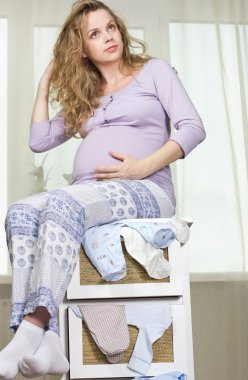 Beautiful cheerful pregnant blonde. Portrait of a young pregnant woman