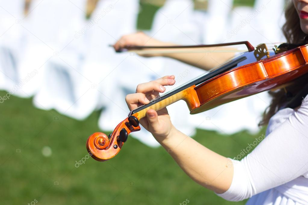 Girl playing on the violin outdoors. Musician for the wedding.Violin under the open sky