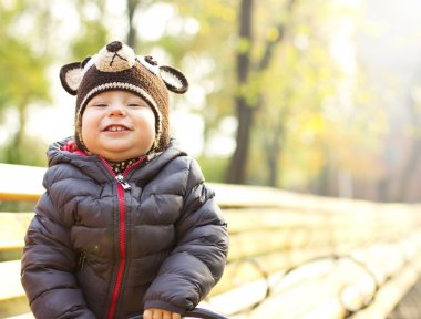 Joyful child in a cap in the form of teddy bear. Happy Child on a walk. The child is in the air in the fall