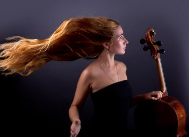 Beautiful girl with a cello on a black background. Cellist. Girl musician.