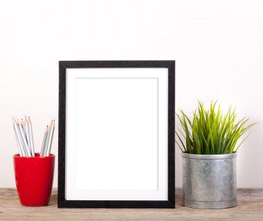 picture frame with office items and pot planr on wooden table