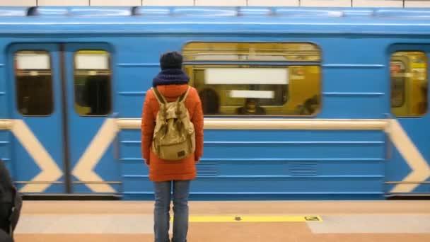RUSSIA, NOVOSIBIRSK - Mar 03, 2020: a metróállomáson várakozó utasnő a peronon. Metro ajtók nyitva