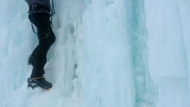 Steigeisen hautnah an den Füßen Eiskletterer auf einem gefrorenen Wasserfall. Eissplitter.