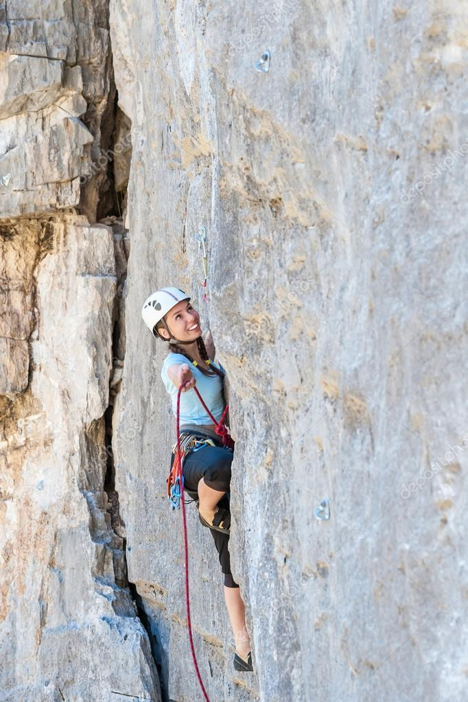Woman climber passes challenging tracks on the rock
