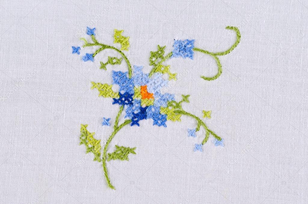Bordado a mano motiv flor azul sobre el blanco mantel de lino ...