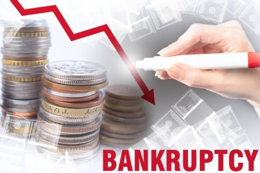 Bankruptcy. A critical drop in revenue. Red arrow down and the word Bankruptcy on the background of money. The person draws a down arrow on the background of coins and bills.