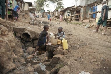 Boys take a water for drinking on a street of Kibera, Nairobi, Kenya.