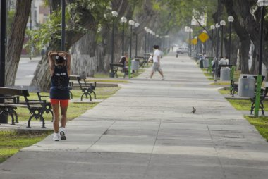 Woman does exercises in early morning on Avenida Arequipa in Lima, Peru.