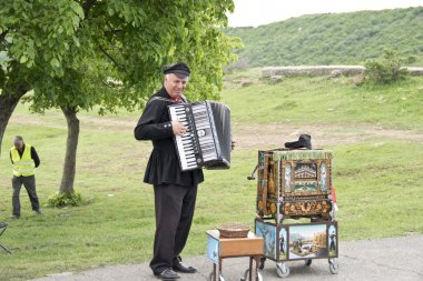 Street musician plays the accordion near the ancient Djvari Church in Mtsketa, Georgia.