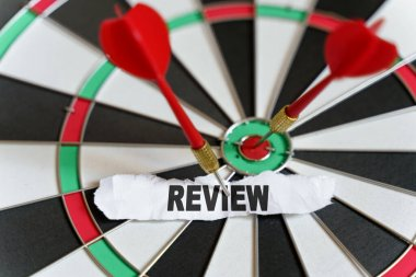 Business and finance concept. A piece of paper with the text is nailed to the target with a dart - REVIEW