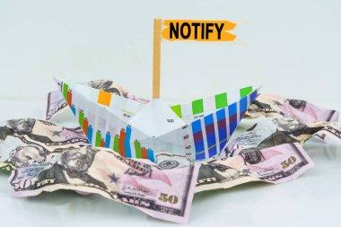 İş ve finans kavramı. İşletme grafiğinden bir kağıt tekne para denizinde yüzer. Metin bayrağa yazıldı - Uyarı