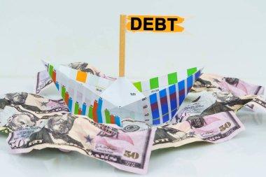 İş ve finans kavramı. İşletme grafiğinden bir kağıt tekne para denizinde yüzer. Metin bayrağa yazıldı - DEBT