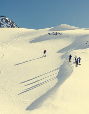 Skiers ascending a mountain slope.