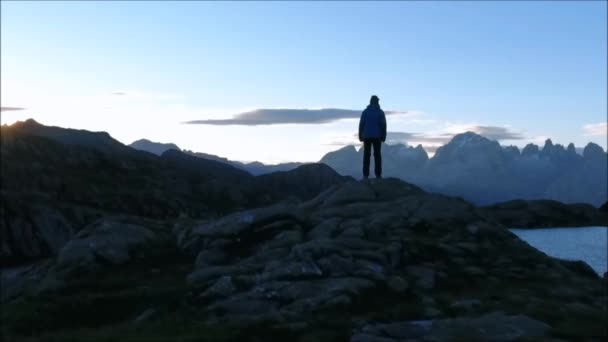 AERIAL: Mountaineer celebrating success, overviewing mountain lake at sunrise.