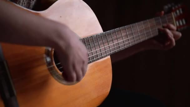 Detailní záběr ženských rukou hrajících na klasickou kytaru. Čas procvičování