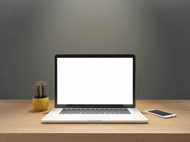laptop and phone with blank screen on desk front gray wall