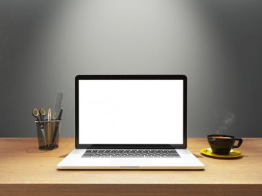 laptop and coffee with blank screen on desk front gray wall