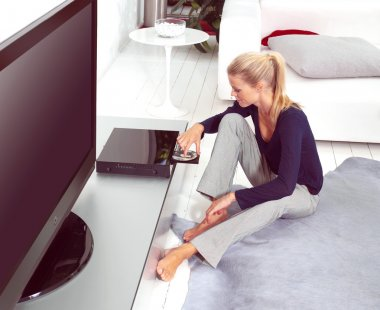 woman using dvd player in flat
