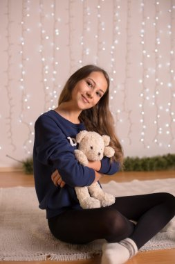 beautiful young girl in a sweatshirt and tights near the Christmas tree, Christmas lights in the background, she smiles, happy, looking directly,white socks, warm socks, a white teddy bear, hugging a pillow,