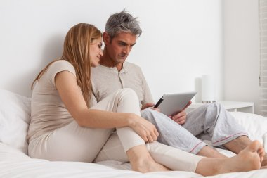 Couple using ipad in bed