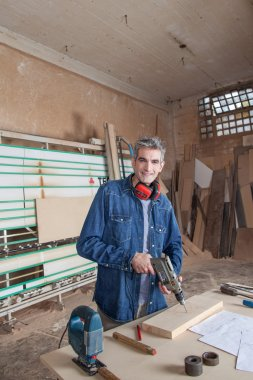 Carpenter at his desk with a drill