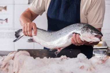 Seller holding a pink salmon