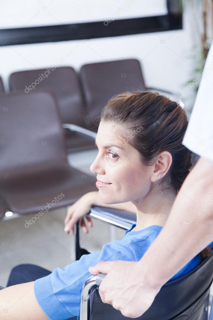 nurse helping a woman in wheelchair
