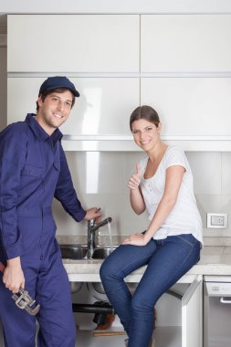 Pair of plumbers showing thumb up