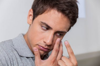 Man putting the contact lenses