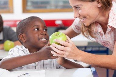 Boy giving to his teacher  apple