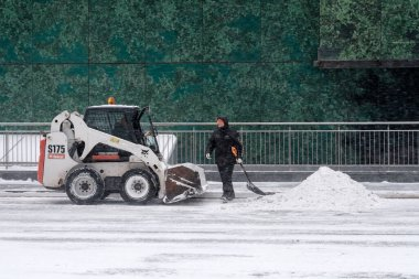 A utility worker and a small loader excavator remove snow from the road