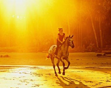 woman riding bareback at sunset