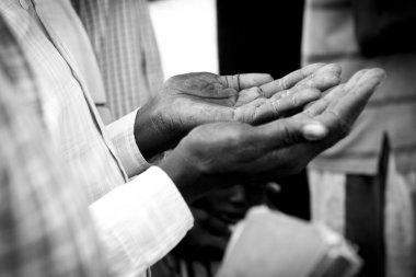 hands of man praying in South Sudan
