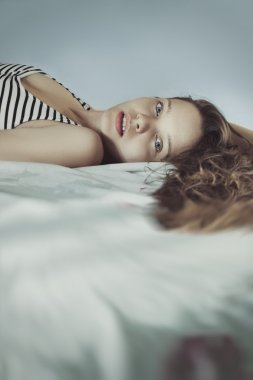 Cute Young woman in bed with long ringlets hairs