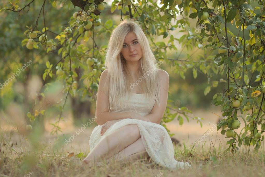 beautiful young woman sedit on the grass under the apple tree