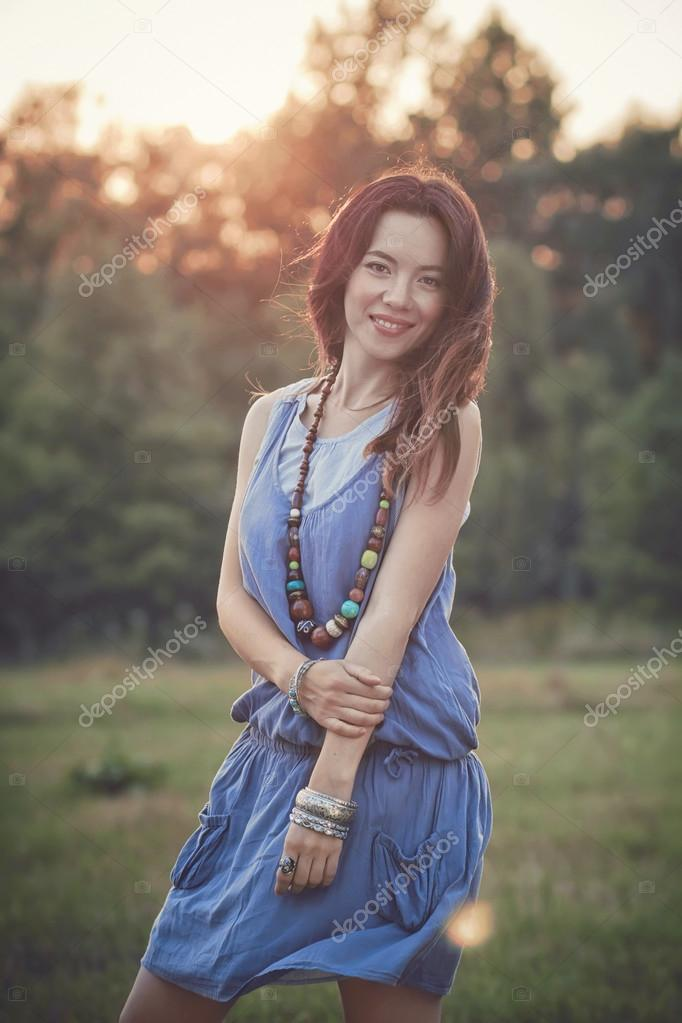 Portrait of the young beautiful  woman outdoors in the field