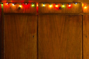 Christmas background with electrovalency on the surface of wood furniture with drawers.