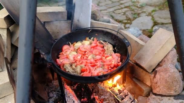 Chakhokhbili grúz étel főzés egy üstben. Tüzet nyitni fából a tűzben. Kőből készült kandalló.