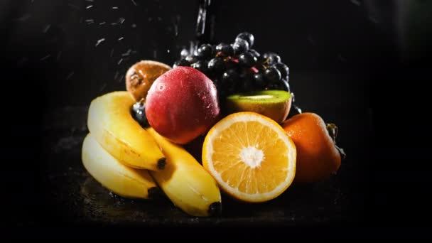 Washing Fresh Organic Fruits by Black Background