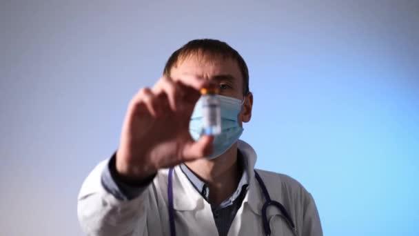 Mužský lékař ovládá lahvičku s koronavirovou vakcínou