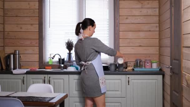 Junge Frau gießt Milch in Becher in der Küche