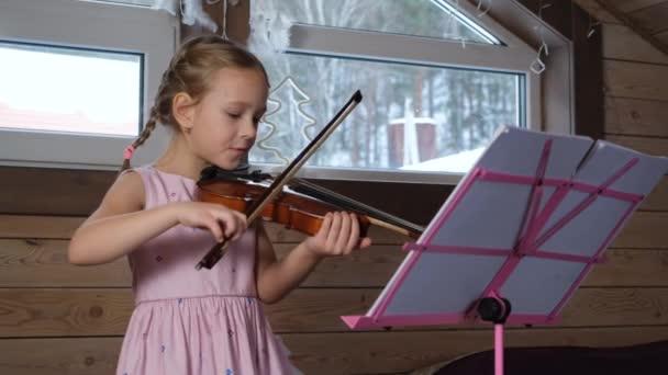 Aranyos kislány hegedül a padláson