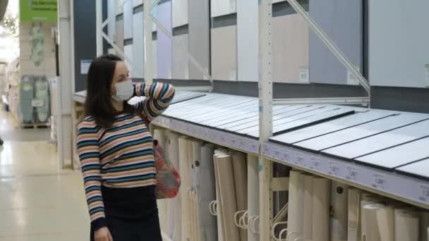 Female Choosing Wallpapers in Building Store