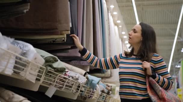 Young Female Choosing Curtains in Textile Shop