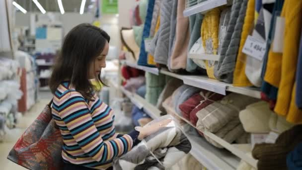 Woman Choosing Soft Plaid in Store for Home