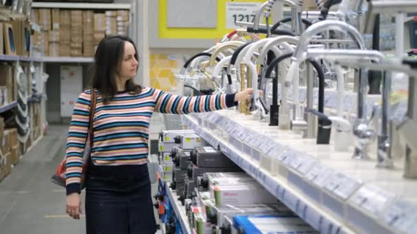 Female Choosing Faucets at a Plumbing Store